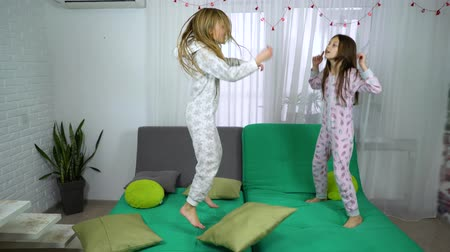 yatak kıyafeti : girls in pajamas dancing on sofa Stok Video