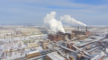 pan shot : aerial view of smoking pipes in industrial zone in winter