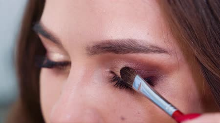 ábrázat : Closeup of hands applying eyeshadows to young woman eyelids in slow motion