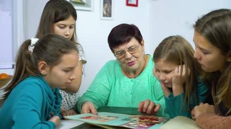 архив : Grandmother and four granddaughters watching old photo album at home