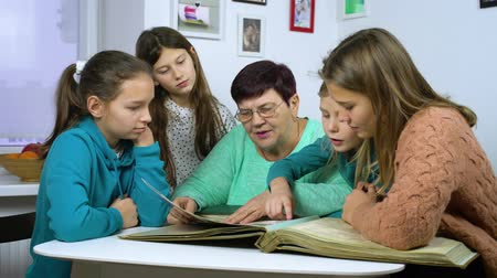 アーカイブ : Grandmother showing old photo album to her granddaughters
