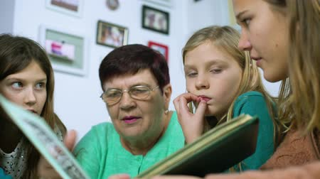 archívum : closeup of grandmother and four granddaughters watching old photo album at home