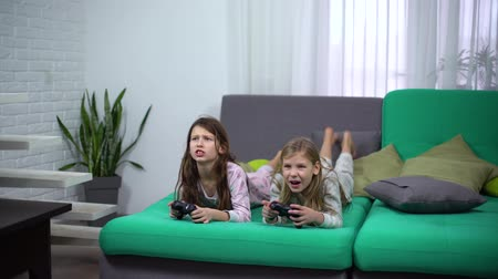 interaktivní : little girls playing with game pads at home