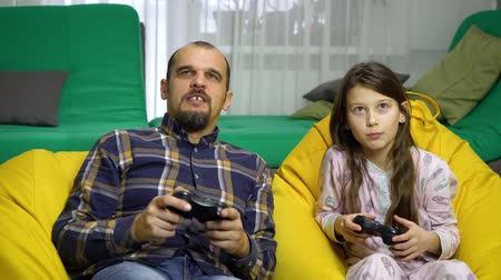 tölt : father and daughter playing gamepads together at home
