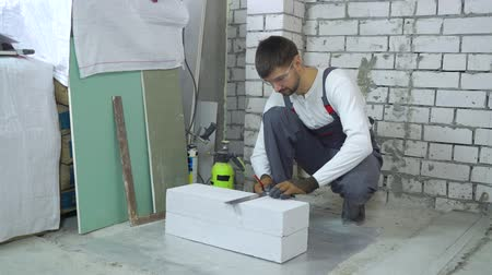 маркировка : construction worker doing markup on aerated concrete block at construction site Стоковые видеозаписи