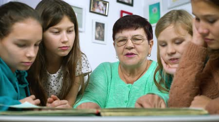 пять : Grandmother showing old photo album to her four granddaughters