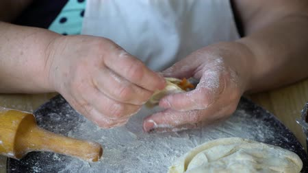 клецка : closeup of elderly woman hands making vegetarian dumplings with roasted cabbage