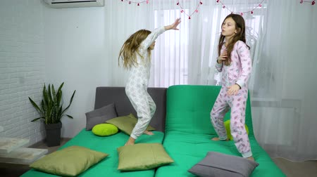 caráter : two little girls in pajamas dancing on sofa