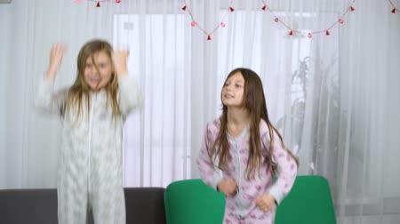 yatak kıyafeti : two cute girls in pajamas dancing on sofa