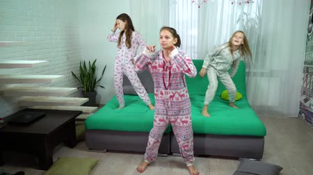 caráter : three cute girls in pajamas dancing at home