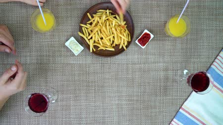 fries : top view of family eating pizza and fries