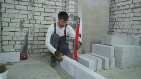 мастер на все руки : construction worker checking block laying with bubble level