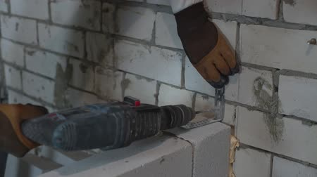 sponka : builder screwing holes in brick wall with electric drill for joining clamp Dostupné videozáznamy