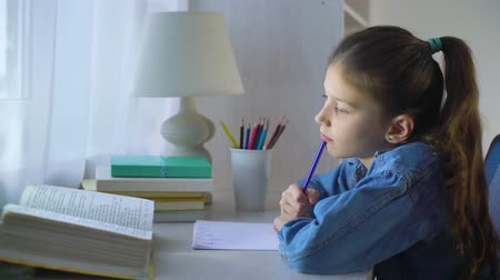 livros didáticos : sad school girl doing homework and feeling exhausted Stock Footage