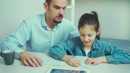 çözmek : father helping his daughter to do homework Stok Video