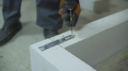 sponka : builder screwing joining clamp in aerated concrete block with electric drill