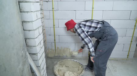 estuque : builder putting plaster on aerated concrete block wall Vídeos
