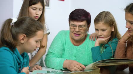photo album : girls watching old photo album with their grandmother