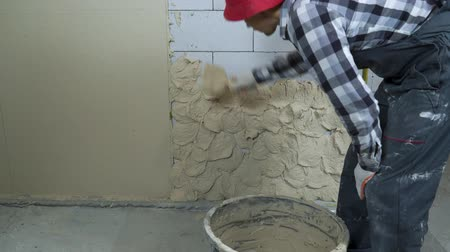 estuque : builder in work wear putting plaster on aerated concrete block wall Vídeos