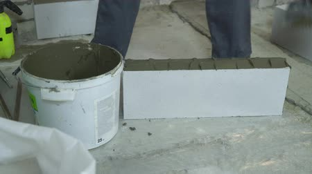 клейкий : builder putting mortar on sides of aerated concrete block with spatula
