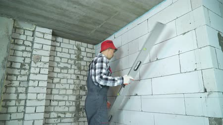 accurate : builder checking markings on aerated concrete block wall with construction ruler