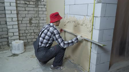 workman : builder spreading plaster on aerated concrete block wall with construction ruler