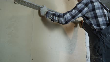 construtor : builder leveling plaster on aerated concrete block wall with construction ruler