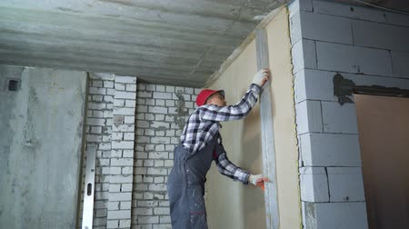 workman : builder smoothing plaster on interior wall with construction ruler