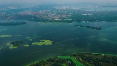 ścieki : aerial of wide river surface covered with green algae near industry zone