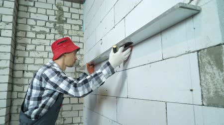 governante : builder applies construction ruler to aerated concrete wall to check its marking