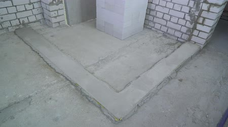 unfinished : pan shot of concrete foundation ready for laying a new brick wall
