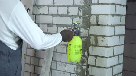 tilt down : construction worker moisturing brick wall with water sprayer