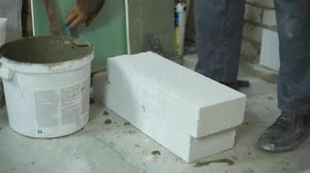 workman : builder measures aerated concrete block with measuring tape and corner ruler Stock Footage