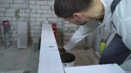 megújít : construction worker checking evenness of aerated concrete wall with bubble level