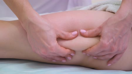 masszírozó : closeup of female hands massaging woman thighs for anti cellulite treatment