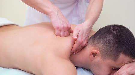 terapeuta : female hands massaging trapezius muscles of male customer in spa salon