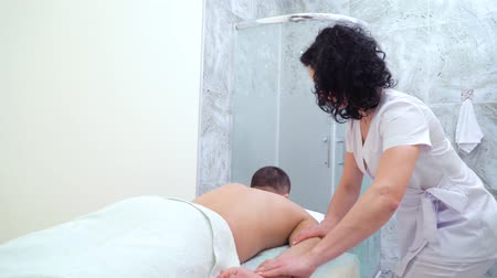 therapeutic : young female masseur doing relaxing massage on male arm in spa salon Stock Footage