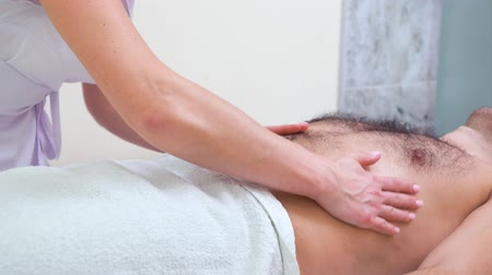 não barbeado : female hands doing relaxing massage on abdomen of male customer in spa salon Stock Footage