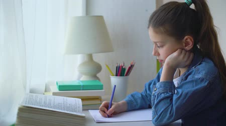 papírnictví : little school girl in jeans jacket doing sums on sheet of paper at home