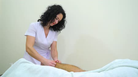 masszírozó : female masseur in uniform massaging man shin in spa salon