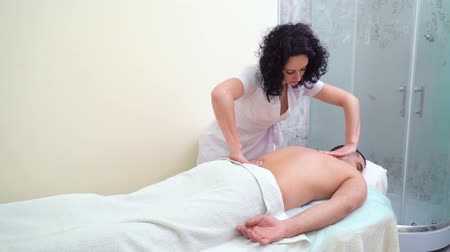 therapeutic : beautiful female therapist massaging back of male customer in spa salon Stock Footage