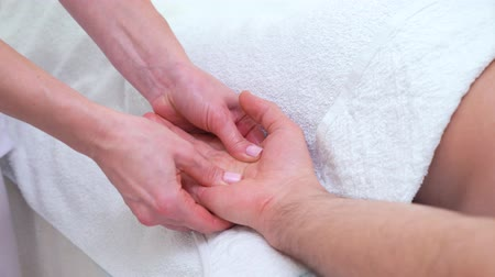 rozmazlování : female hands doing palm relaxing massage for male patient in therapeutic room