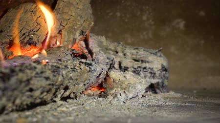 firebox : closeup pan shot of wood logs burning and breaking in fireplace in slow motion
