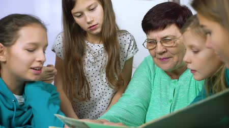 archívum : girls watching old photo album with their grandmother
