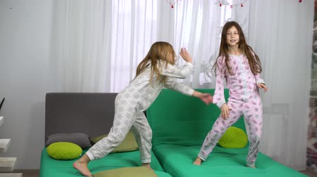 yatak kıyafeti : two little girls in pajamas dancing on sofa