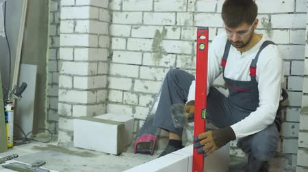 мастер на все руки : builder fixing brick laying with rubber hammer according to bubble level