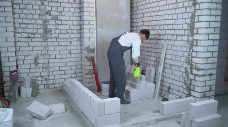 püskürtücü : young male builder moisturing block with water sprayer before laying it Stok Video