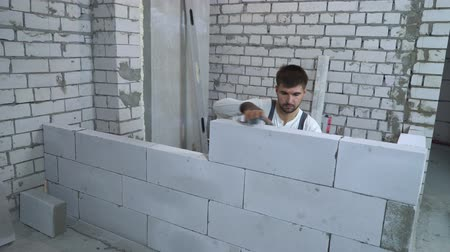 cuidado : young caucasian builder checking evenness of newly built wall with bubble level