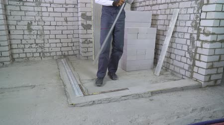 стандарт : builder makes measurements on concrete base with corner and construction rulers
