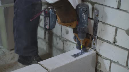 sponka : view of builder hands fixing joining clamp to brick walls with electric drill Dostupné videozáznamy